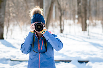 Woman photographer in winter forest