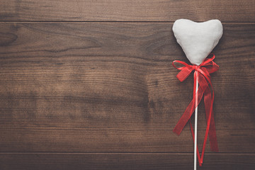 white plush heart shape on sticks over wooden background