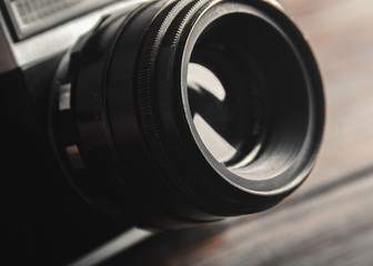Vintage film camera lens on wooden table. Close up.