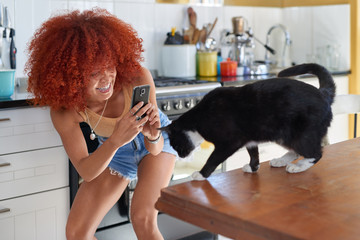 Smiling woman trying to take a photo of her pet cat