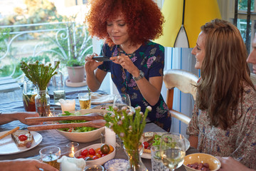 pretty woman takes photo of food at party to share on social media