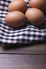 Eggs on red and white tablecloth. Wood table. Horizontal shoot.