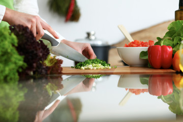 Close-up of human hands cooking vegetables salad in kitchen on the glass table with reflection. Healthy meal and vegetarian concept