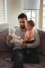 Father and baby playing with teddy bear on sofa in living room