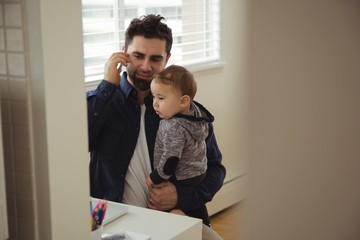 Father talking on mobile phone while holding his baby