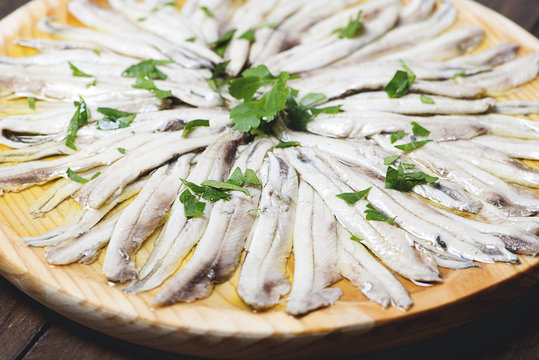 Close-up of anchovies with olive oil and vinegar on wooden plate. Healthy food.