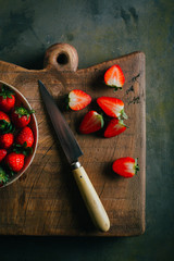 Cutting strawberries on wooden cutting board over grunge background