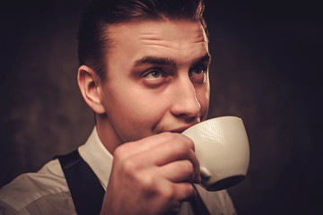 Sharp dressed man wearing waistcoat with a cup of coffee