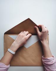 Big brown vintage envelope with woman hands.