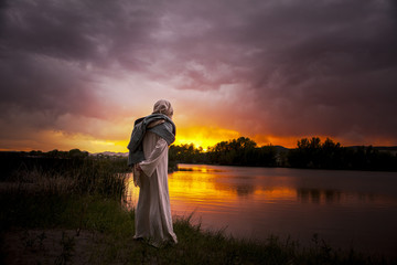 Jesus Christ overlooking a sun setting on the lake Wall mural