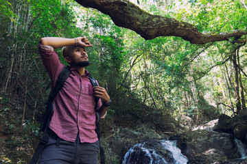 happy young man hiking in autumn forest