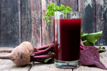 Beet juice in a glass against a rustic wooden background