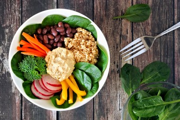 Healthy lunch bowl with quinoa, hummus and mixed vegetables, overhead scene on a rustic wood background