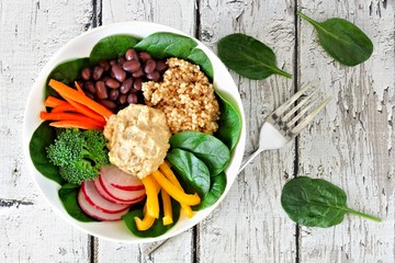 Healthy lunch bowl with quinoa, hummus and mixed vegetables, overhead scene on white wood