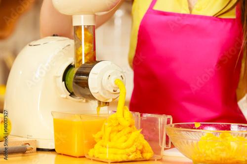 Woman making orange juice in juicer machine immagini e for Cucinare juicer