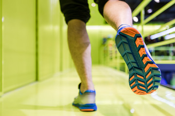 Running sport. Man runner legs and shoes in action on colorful corridor.