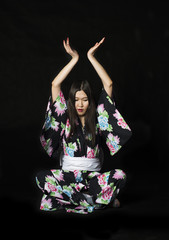 Japanese girl in traditional Japanese kimono on black background.