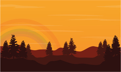 Silhouette of hill with rainbow at sunset