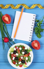 Greek salad with vegetables, centimeter and notepad for notes, healthy food and slimming concept