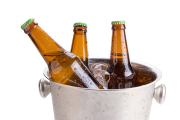 cold bottles of beer in bucket with ice on white background.