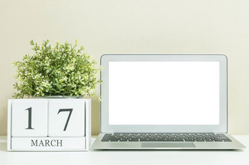 White wooden calendar with black 17 march word with white blank space at center of computer notebook on white wood desk and cream wallpaper textured background , selective focus at the calendar