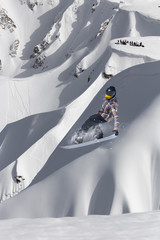 Extreme winter sport. Snowboarder jumping in snowy mountains.
