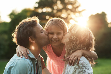 Parents kissing their smiling little girl on her cheeks outside