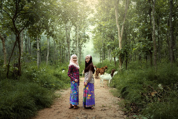 Women dressed in traditional Muslim dress Goat work in the wild North of Thailand and South