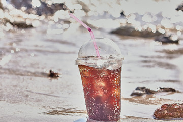 Cola or Cuba Libre cocktail drink with ice on the beach