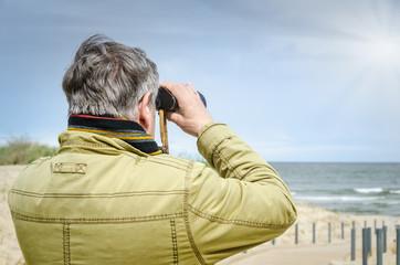 Mann mit Fernglas blickt auf Meer