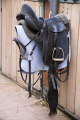 Leather saddle for equestrian sport hanging in the barn
