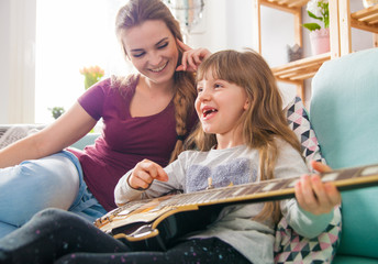 Mother and daughter at home, playing guitar and singing