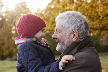 Grandfather Cuddling Granddaughter On Autumn Walk