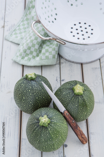 runde zucchini mit einem lochsieb und einem messer auf einem alten weissen holzuntergrund. Black Bedroom Furniture Sets. Home Design Ideas
