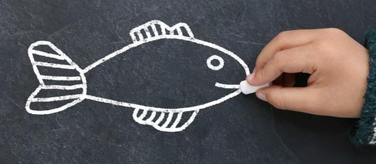 Enfant dessinant un poisson à la craie sur une ardoise