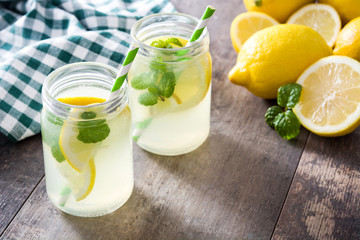 Lemonade drink in a jar glass on wooden background. Copyspace.