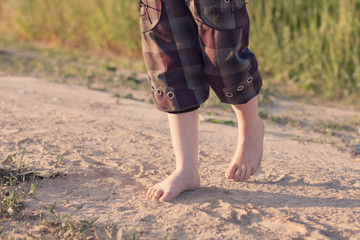 The kid is walking barefoot along the road