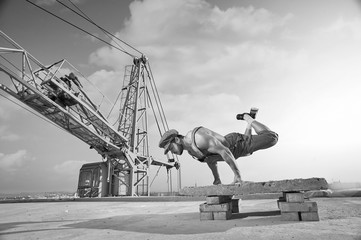 Athletic strong muscular builder doing a handstand on the roof o