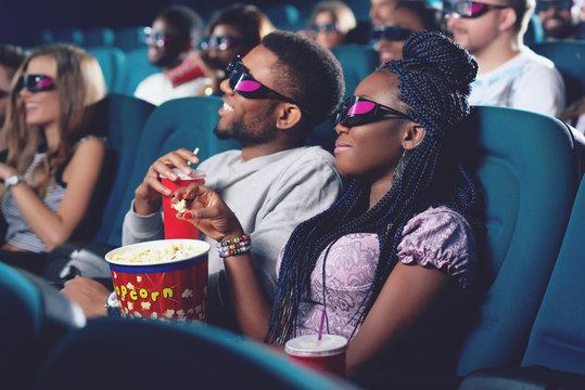 Boyfriend and girlfriend in 3d glasses watching movie in cinema.