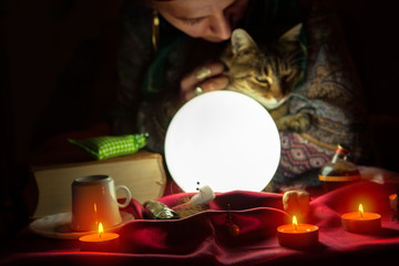 Fortuneteller during session with crystal ball and cat