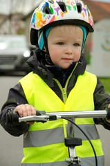 Little child learns to ride a bike on the road. There is a car in the background. Boy is marked by yellow reflective vest and helmet because of visibility and safety.