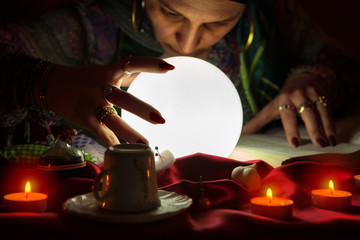 Gypsy fortuneteller gazes into crystalball,using sorcery