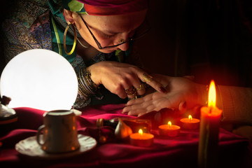 Gypsy woman reading the lines in a woman hand