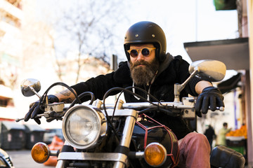 Portrait of bearded biker wearing helmet and sunglasses sitting on his motorcycle