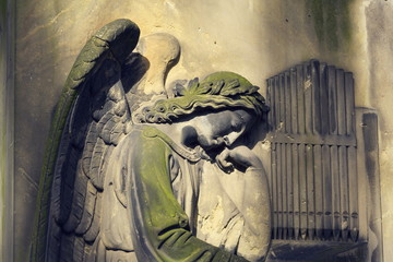 Crying angel organist statue on Malostransky cemetery, Prague, Czech republic