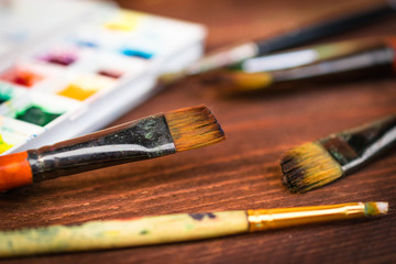 artist workplace with colorful dye and instruments,  brushes on wooden table close-up