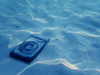 Compact camera on the sand with light reflected under the sea water.