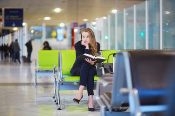 Woman in international airport terminal, reading book