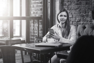 Monochrome image.Young woman sits at table in cafe and use smartphone.On table is cup of coffee and closed notebook