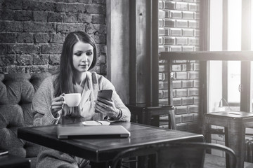 Monochrome image.Young woman with long hair sits at table near window in cafe, drinking coffee and use smartphone.